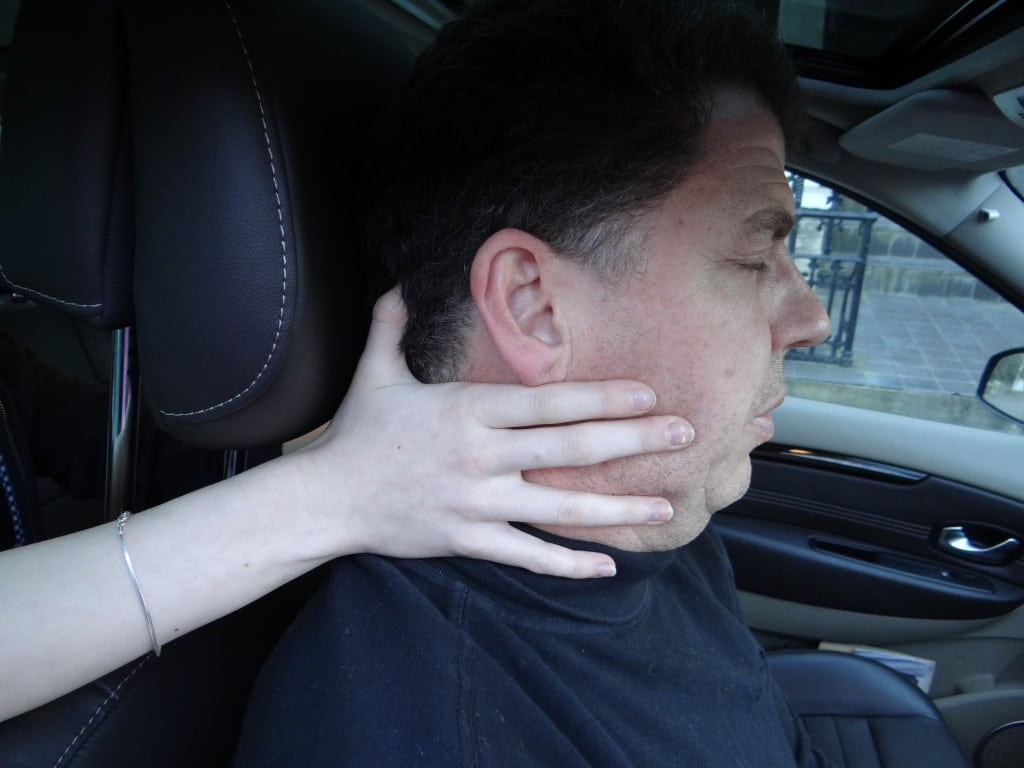Supporting the head of an unconscious casualty in a car